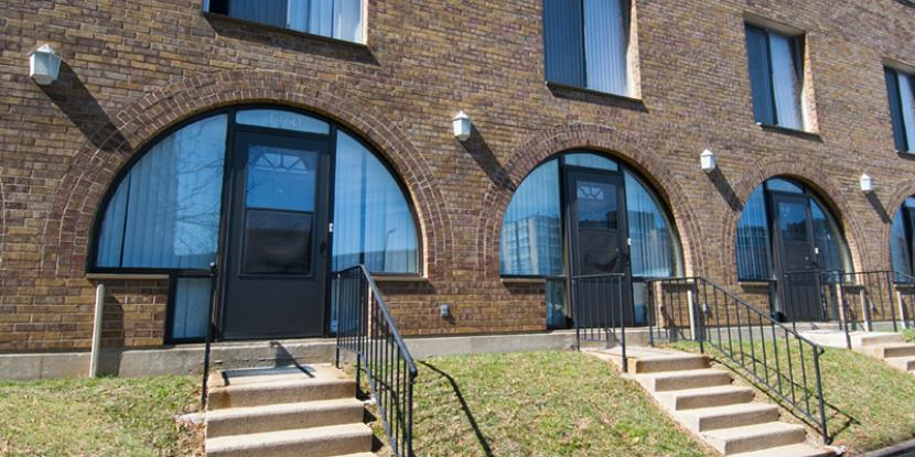 A photo of a brick apartment building centering three entryways, each with a set of stairs.