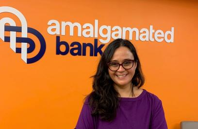 Brenda Loya stands in front of a sign of Amalgamated Bank's logo