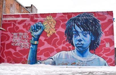 "A mural of a Black boy from the shoulders up. He has short locs and is holding a bouquet of yellow flowers against a pink background. Text beside the boy reads ""they tried to bury us, they didn't know we were seeds."""