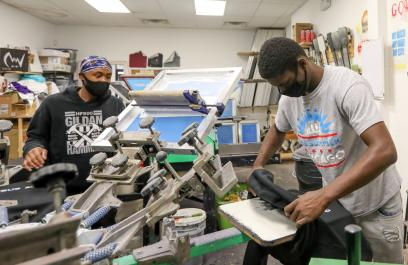 Two masked young Black people focused on their work at a screen printing shop, with a printing machine between them. They are in a white-walled room full of art and printing materials.