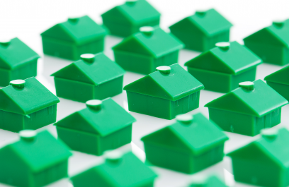 Green, little toy houses from the Monopoly game