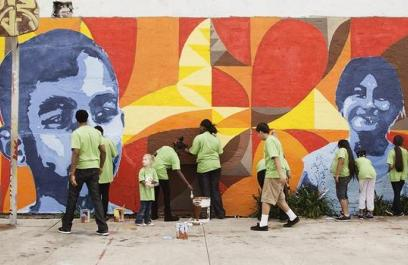 A diverse group of people work together to paint a colorful mural