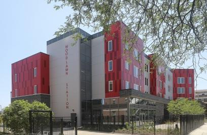 "A photo of a red and white apartment building. The photo contains the entire building, which reads ""Woodlawn Station"" down one face."